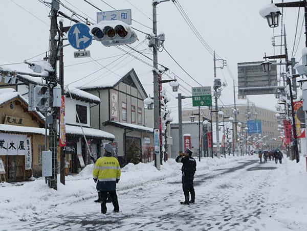 信号機の雪を落とす警察官